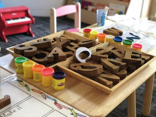 Table with wooden letters and play do